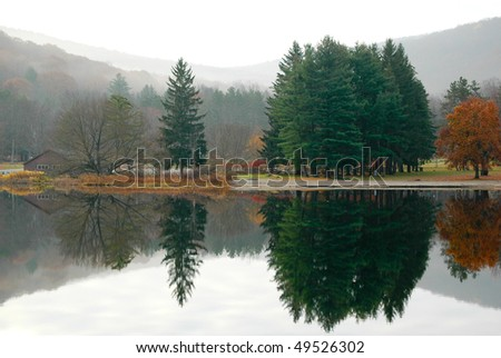 foggy forest and hills beside a lake