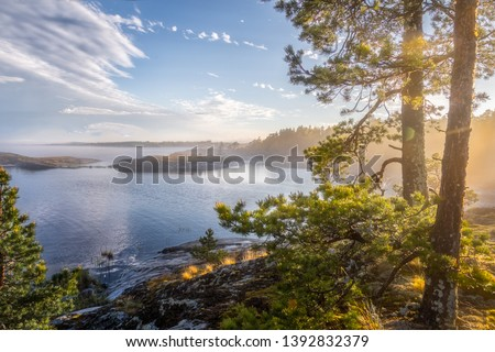 Foggy landscape of northern nature. Magnetic sunny view of the islands and fjords. Awesome sunrise on the lake. Ladoga lake. Smoky summer landscape. Primeval Russia. Archipelago. Republic Karelia.