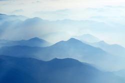 foggy morning in italian mountains - silhouettes on maintain range