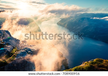 Foggy morning view of popular Norwegian attraction Preikestolen. Great summer scene of the Lysefjorden fjord, located in the Ryfylke area in southwestern Norway. Beauty of nature concept background.