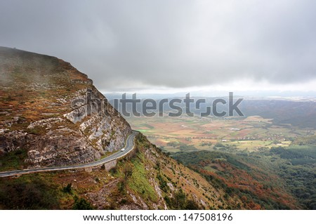 foggy mountain pass with a road and a car climbing