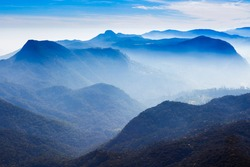 Foggy mountains aerial panoramic view from the Adams Peak or Sri Pada on sunrise. Adams Peak is a tall and holy buddhist mountain in Sri Lanka.