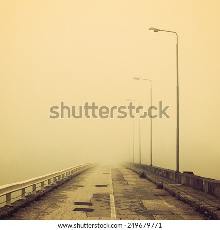 Foggy old road in the morning. Toned photo, vintage filter.