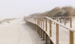 Foggy photo of wooden footbridge of Costa Nova beach in Aveiro, Portugal