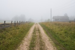 Foggy rural landscape. View of a deserted country dirt road and old wooden houses in the fog. Grass on the roadside. Misty morning in the countryside. Summer in the village. Vologda region, Russia.