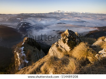 Foggy valley and snowy high mountains.
