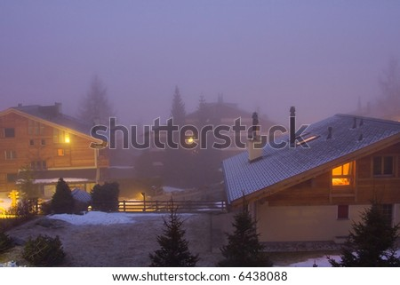 Foggy view on snowy Swiss chalets