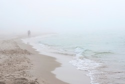 Foggy weather by the sea. Baltic beach in Leba, Poland. Couple walking along coastline. Baltic beach in Leba, Poland.