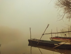 Foggy winter scenery at the lakeside with fishingboats.