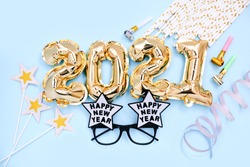 Foil balloons in the form of numbers 2021 and festive glasses on blue background. New year party decoration. Top view