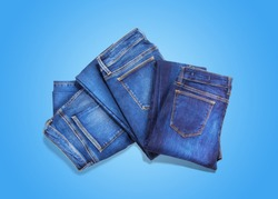 Folded blue jeans on blue background. Denim concept