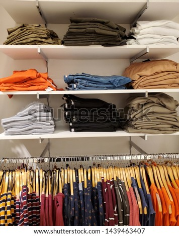 Folded clothes and clothes hanging on racks in a store