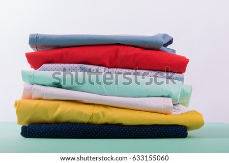 Folded colorful pants and jeans. Stack of bright female trousers. Close up #633155060