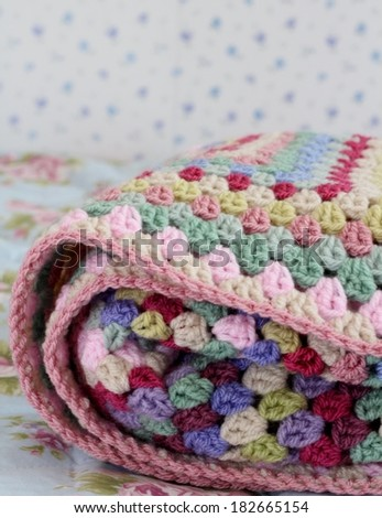 Folded crochet afghan blanket in shabby chic bedroom, granny stitch in yarn of pink, cream, pink, purple and cream