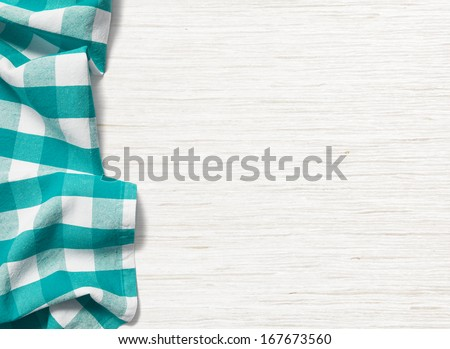 folded cyan tablecloth on bleached wooden table
