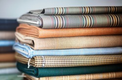 Folded fabrics for interior decor or garment making by a tailor or seamstress in a neat stack in a shop or studio