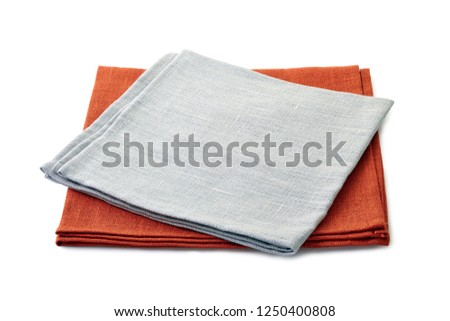 Folded gray and brown textile napkins stacked on white background