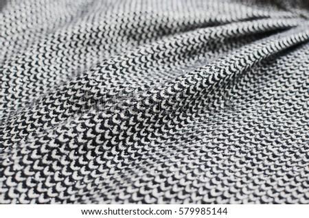 Folded grey tweed fabric textile close up.  #579985144