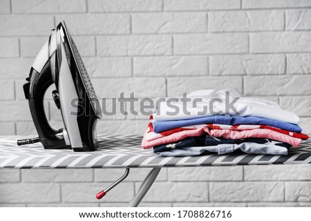 Folded ironed men's shirts lie next to the iron on the ironing board.