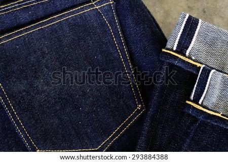 folded men\'s denim jeans / close up on folded men\'s denim jeans with folded on semen floor