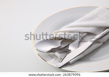Folded napkin with fork, spoon and knife, on plate #263879096