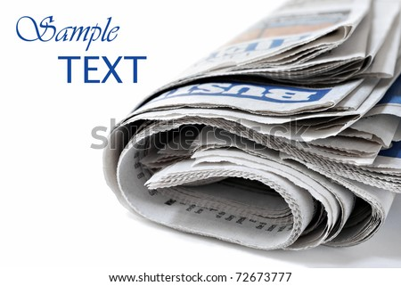 Folded newspaper on white background with copy space.  Macro with shallow dof.  Focus on page edges.