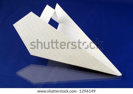 folded paper plane over blue background