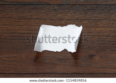 Folded piece of note pad paper, opened on old wooden desk. Isolated on white.