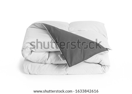 Folded soft white duvet, blanket or bedspread with the gray back side and empty white label, against white background. Close up photo Stockfoto ©
