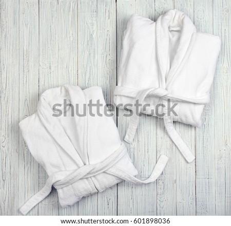 Folded spa bathrobes on wooden background