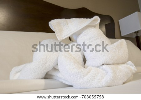 Folded terry cloth towels in shape of dog on hotel bed. #703055758