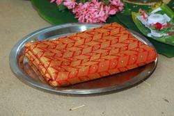 Folded traditional Kerala kasavu saree and red silk saree on a dish during Indian weddin