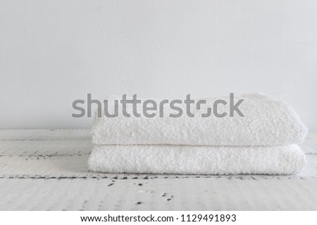 Folded two white towels on a white wooden table. Spa and wellness, cotton terry textile. Ecological theme #1129491893