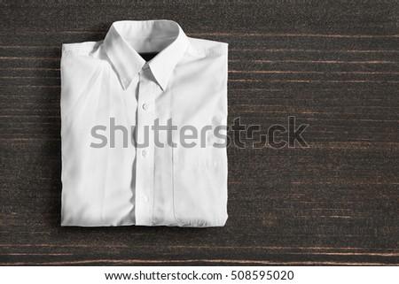 Folded white basic shirt on dark wooden background