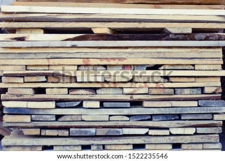 Folded wooden brown and gray planks. A pile of boards stacked on top of each other. Wooden boards, lumber, industrial wood, timber. Pine wood timber