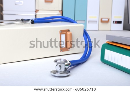 Folder file, stethoscope and note on the desk. blurred background. #606025718