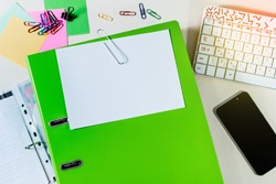 Folder with white paper for notes, and office supplies, keyboard, mobile phone, on desk. Concept of education.