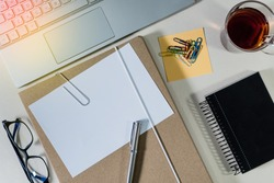 Folder with white paper for notes, and office supplies, Tea cup, notebook, keyboard, on desk. Concept of education.