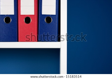 Folders for documents in white bookcase