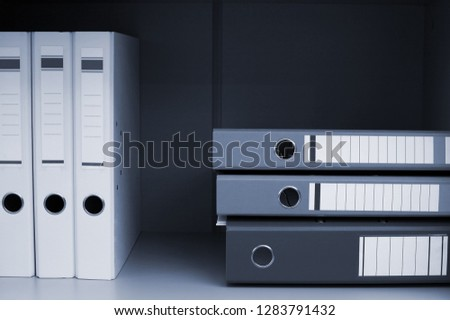 Folders for documents on book shelf at office
