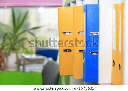 Folders in office. Folders on office window background. #671673685