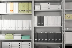 Folders with documents on shelves in archive