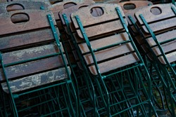 Folding chairs made from steel and wood standing in collapsed in multiple rows.