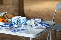 Folding furniture for a picnic in the forest, a chair and a table covered with disposable dishes with the symbols of Israel (with the inscription Israel in Hebrew). Yom Haatzmaut IDF