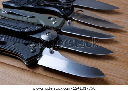 Folding knives on a wooden background.