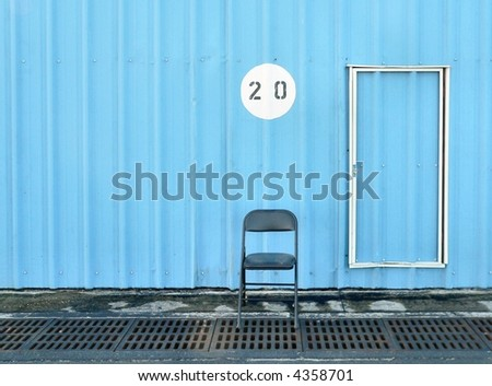 Folding metal chair sits empty beside door numbered with twenty in blue steel building. In front of the chair are steel storm drains. Only half the door is visible. The chair is directly below the 20.