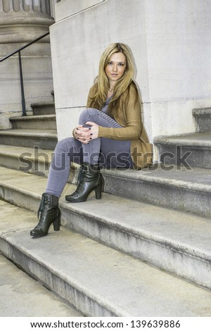 Folding one leg, a young pretty woman is sitting steps to relax./Take a Break