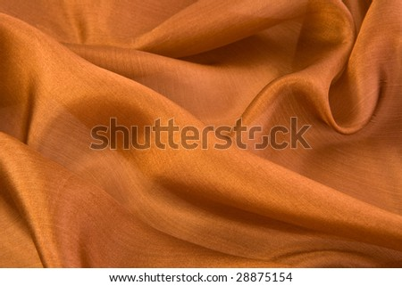 Folds on brown aglint silk close-up