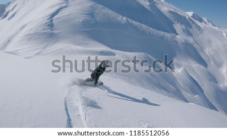 Stock Photo FOLLOW: Female snowboarder carving down the fresh powder snow in wintry Alps. Girl freerider snowboarding freshly fallen snow off piste in high mountains. Snowboarder riding untouched snow blanket