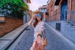 Follow me concept and traveling together. Happy smiling joyful young girl traveler holds the boyfriend's hand and taking photo on a phone camera during vacation weekend time while sightseeing